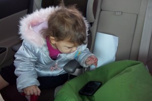 Cydnee watches cartoons on dad's cell phone on a long winter drive home from Calgary